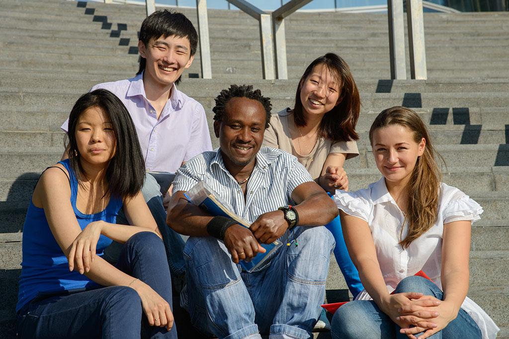 Multiethnic group of university students sitting on steps