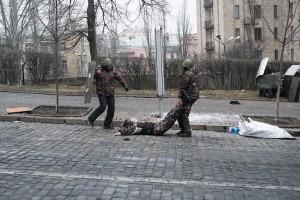 Андрій Юркевич допомагає витягти з-під обстрілу пораненого Володимира Гончаровського. Фото Eric Bouvet