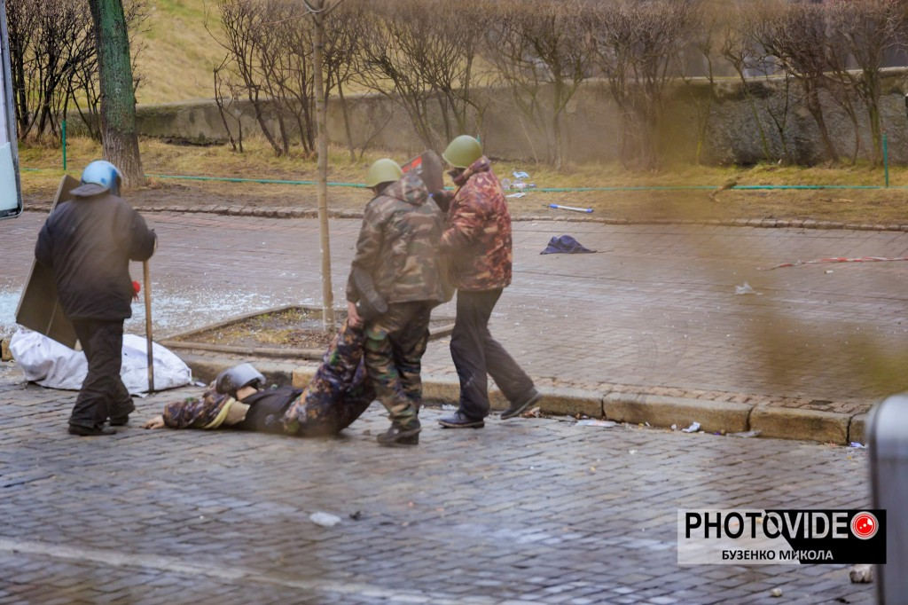 Андрій Юркевич допомагає витягти з-під обстрілу пораненого Володимира Гончаровського. Фото: Володимир Бузенко.