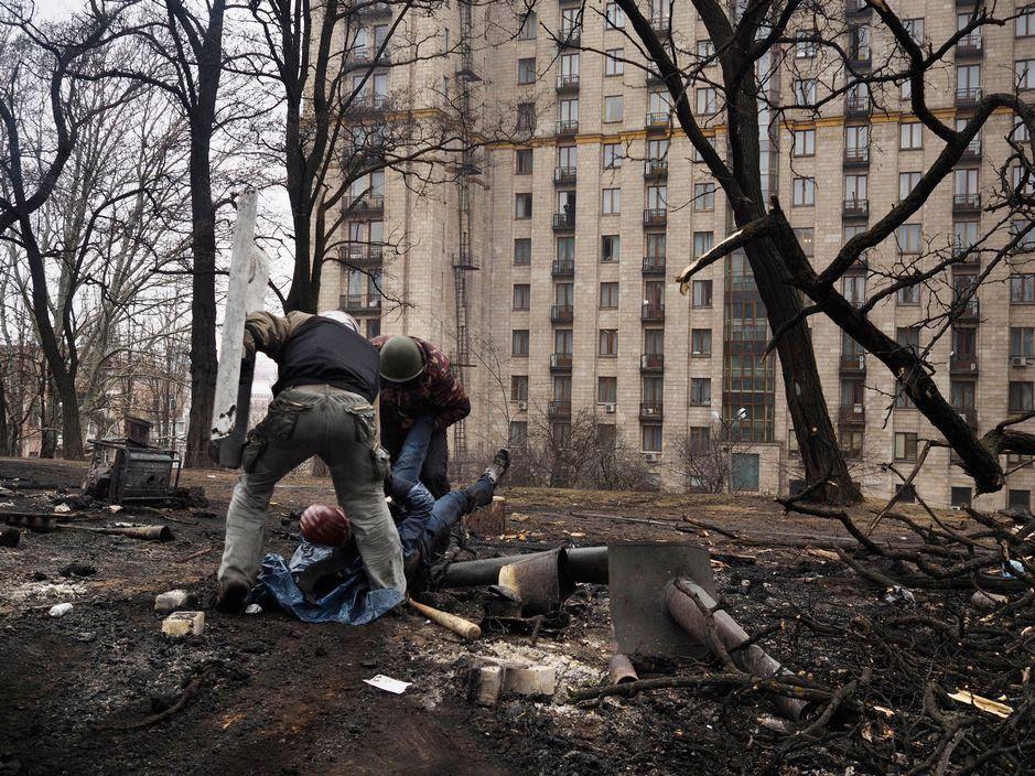 Андрій Юркевич допомагає витягти з-під обстрілу пораненого. Автор фото невідомий.