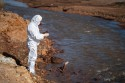 A scientist in a white protective suit takes samples of water from a polluted river.