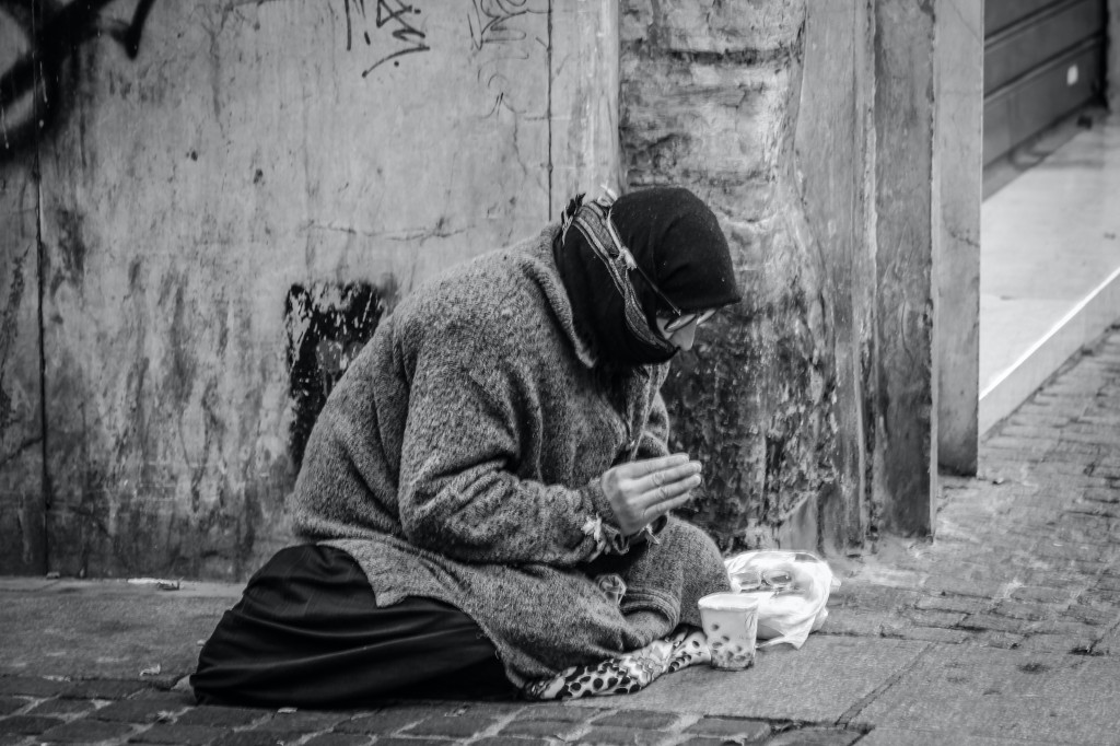 grayscale-photography-of-man-praying-on-sidewalk-with-food-1058068