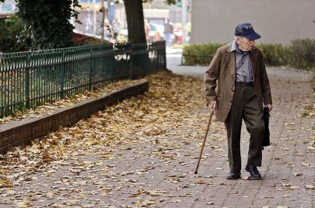photo-of-elderly-man-walking-on-pavement-3093287