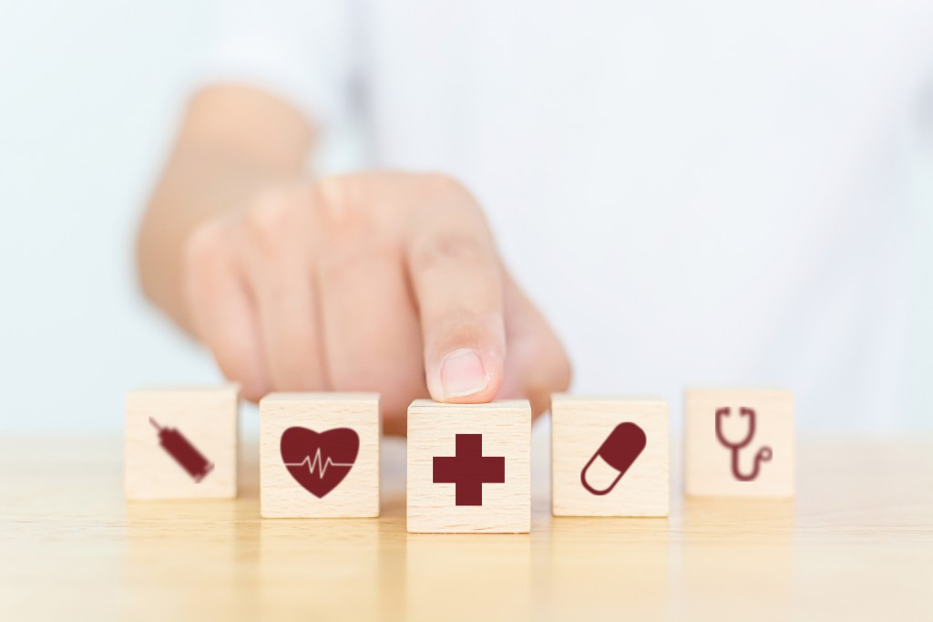 Wood block with icon healthcare medical, Insurance for your health concept