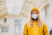Close up portrait of a young blonde in medical protective mask, yellow coat and knitted cap paralyzed with fear by news about virus cover-19. Coronavirus pandemic concept.