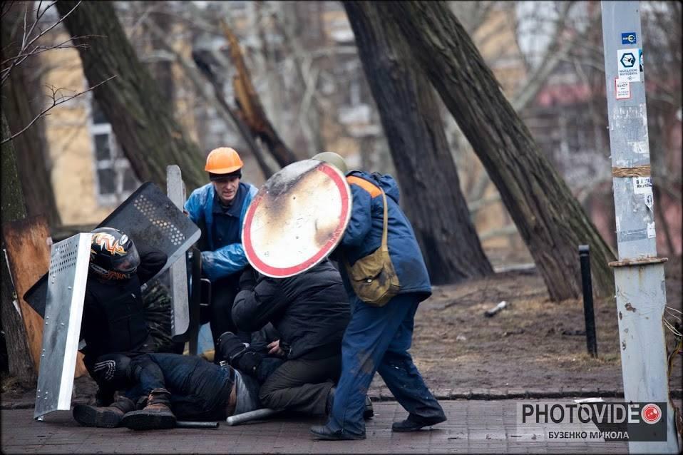 Побратими прикривають щитами пораненого Василя на Інститутській. Фото: Микола Бузенко.