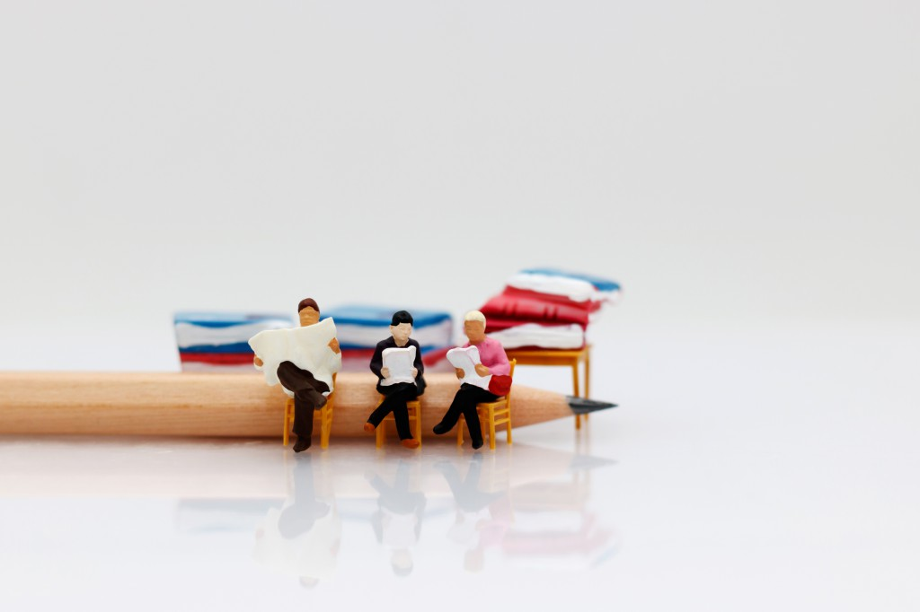 Miniature people reading  book with pencil, education or business concept.