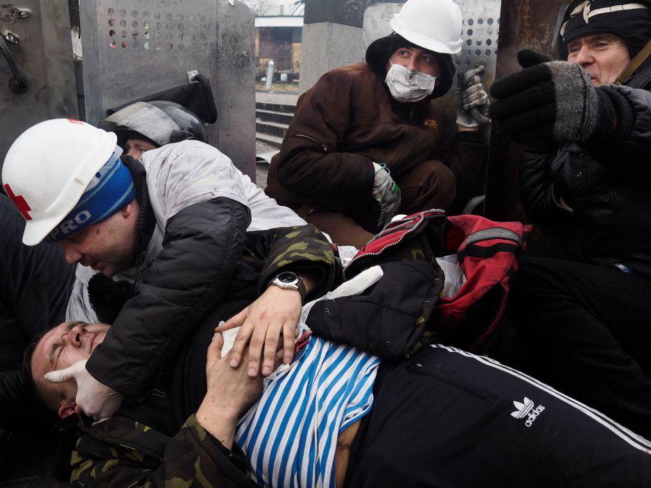 Медик-волонтер Євген Воленко рятує пораненого Івана. Праворуч у чорному одязі Олександр Царьок, який загине на цьому ж місці через декілька хвилин. Фото: Jérôme Sessini.