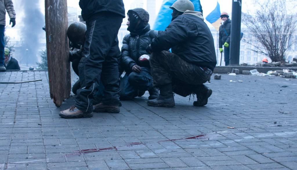 Іван (в центрі) з пораненою рукою біля Жовтневого палацу 20 лютого. Фото: Alan Turgutoglu.