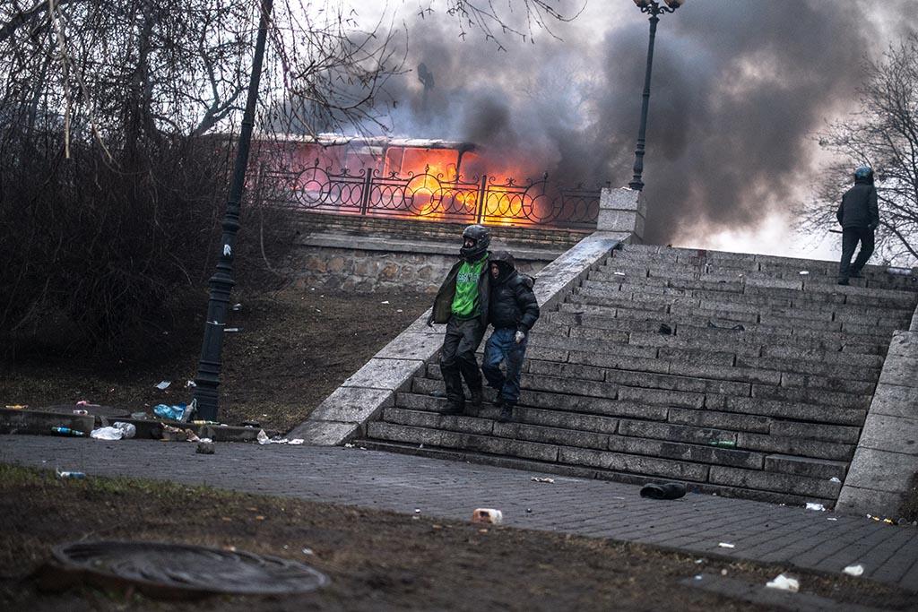 Іван Пантелєєв допомагає спуститися пораненому біля Жовтневого палацу 20 лютого. Фото: Eric Bouvet.