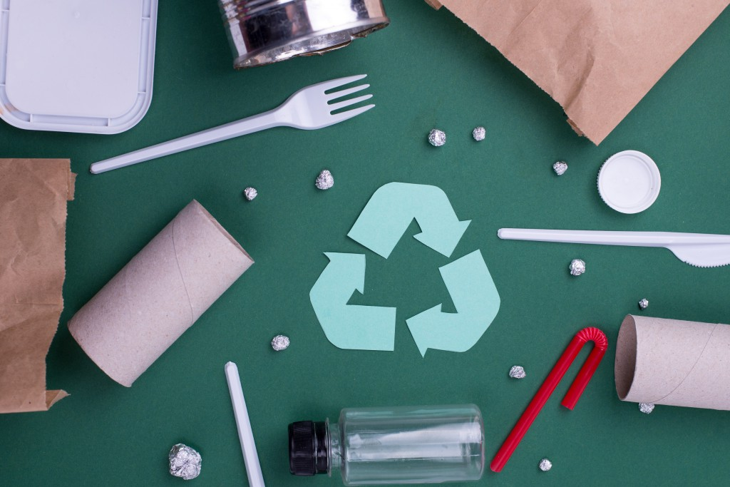 Reuse reduce recycle flat lay concept with plastic, paper, and polyethylene waste. Ecology background image with recycling symbol.